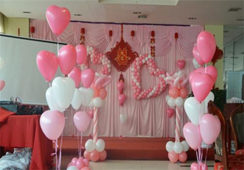因为,它里面运用了许多爱心气氛来烘托气氛,而舞台墙面粉白气球组成的