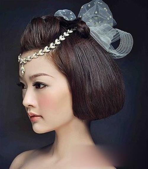 四、手推波纹短发新娘造型会给人一种高雅又复古的感觉,凸显出的气质一定会是精致无比的。这款造型能够将新娘脸部的轮廓线条很好的修饰,一种圆润又光洁的美感就这样展现出了。不过,侧分款式的短发新娘造型更能够美出一种新的境界哦! 短发新娘发型图片