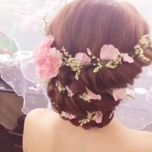 找两束头发分别束起,然后把发尾做成卷,再把鲜花围绕在两束头发的发根图片